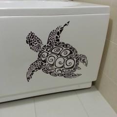 Вырезанная из тёмной полимерной плёнки черепашка на ванну